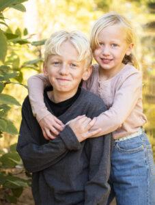 utomshufoto i skog, kvällssol, barnfotografering utomhus, syskonfoto